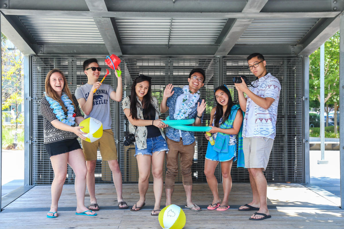 STCs posing together in tropical clothing and holding props